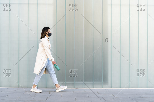 Businesswoman with bottle walking on footpath by glass wall during pandemic
