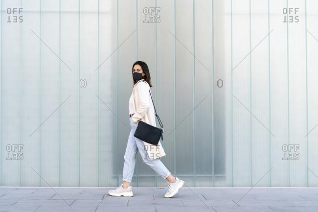 Female entrepreneur walking on footpath by glass wall during coronavirus
