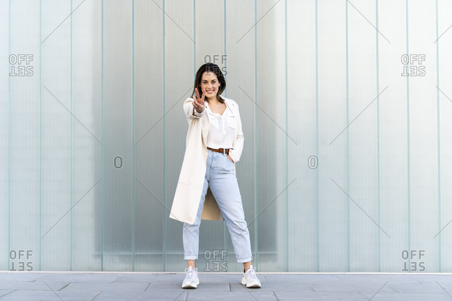 Smiling female entrepreneur doing peace sign while standing against glass wall