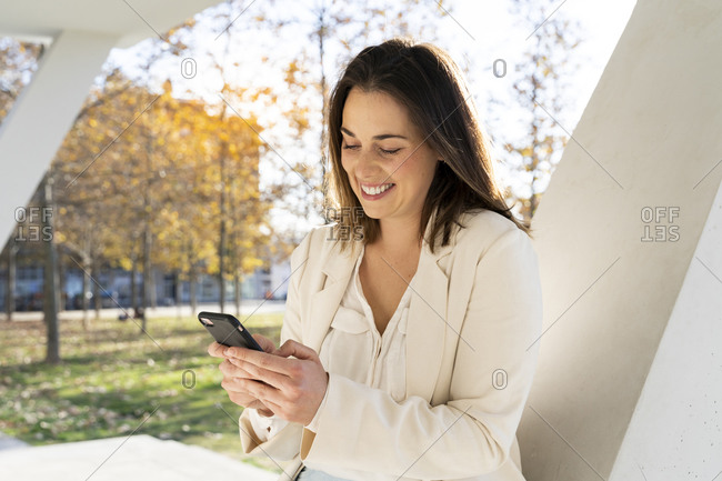 Businesswoman text messaging on smart phone in park