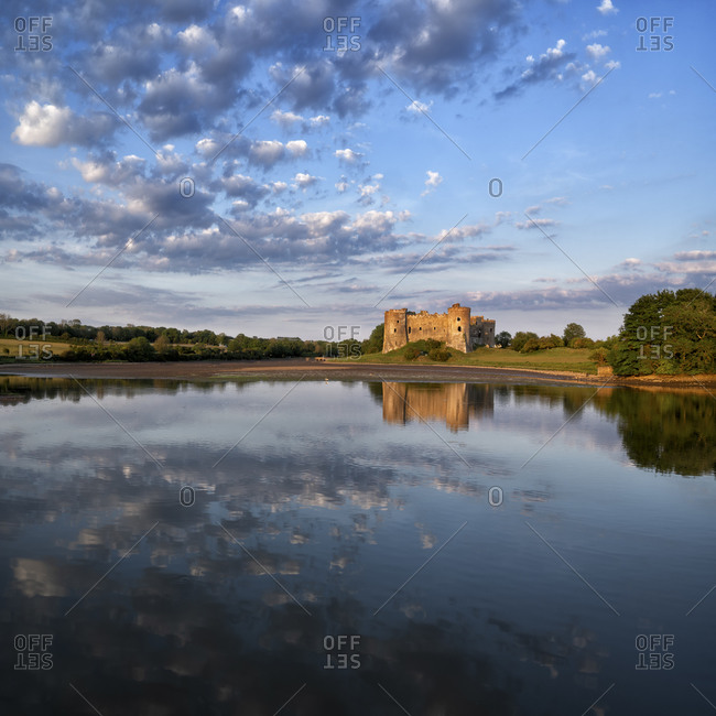 UK- Wales- Pembrokeshire- Clouds reflecting on shiny surface of Carew River at dusk with Carew Castle in background