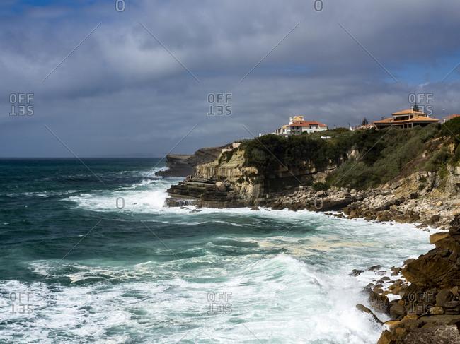 Portugal- Lisbon District-Azenhasdo Mar- Waves splashing below cliffs of seaside town