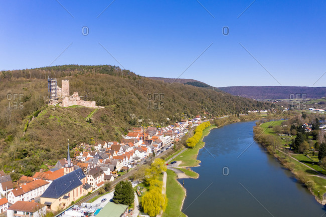 Germany- Bavaria- Stadtprozelten- Helicopter view of riverside town in autumn with Henneburg castle in background