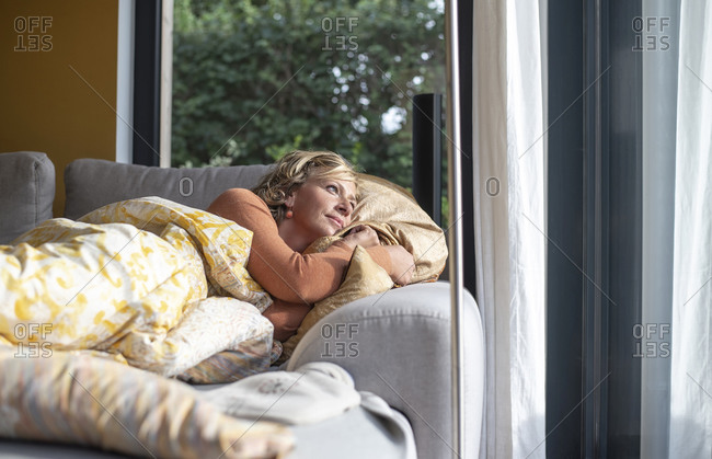 Thoughtful woman looking through window while lying on sofa at home