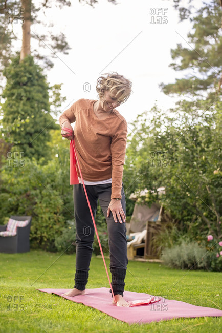 Woman stretching resistance band while exercising at back yard