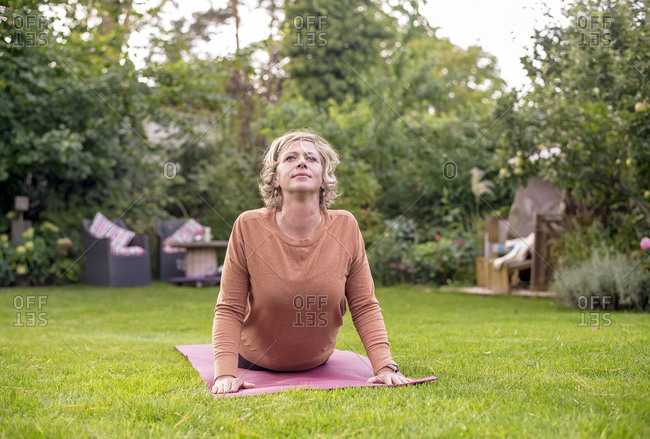 Woman doing yoga while lying on exercise mat at back yard