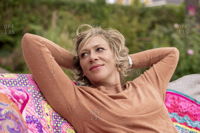 Smiling woman sitting with hands behind head on sofa at back yard