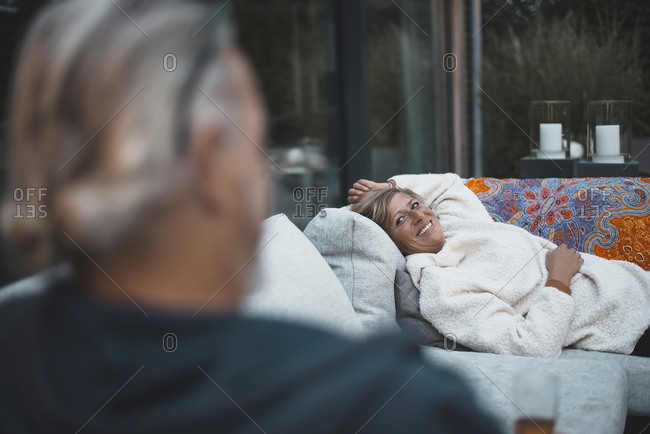 Smiling woman looking at man while relaxing on sofa at backyard