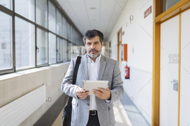 Mature male professor holding digital tablet in corridor at university