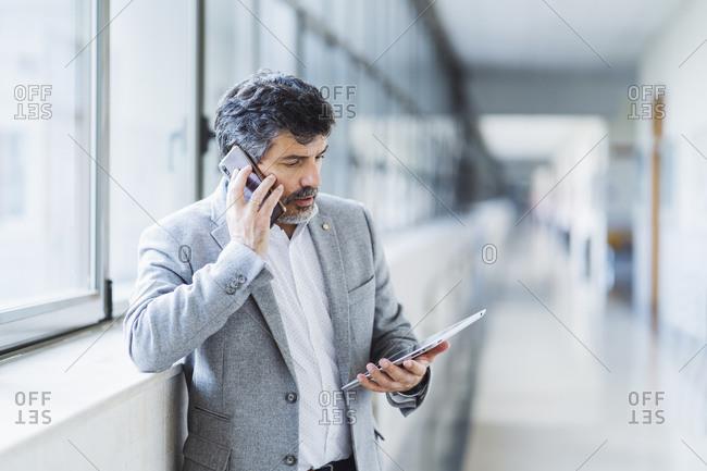 Male professor talking on mobile phone while looking at digital tablet against window in university corridor