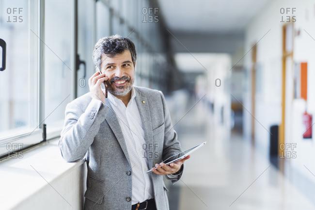 Smiling professor looking away while answering phone in corridor at university