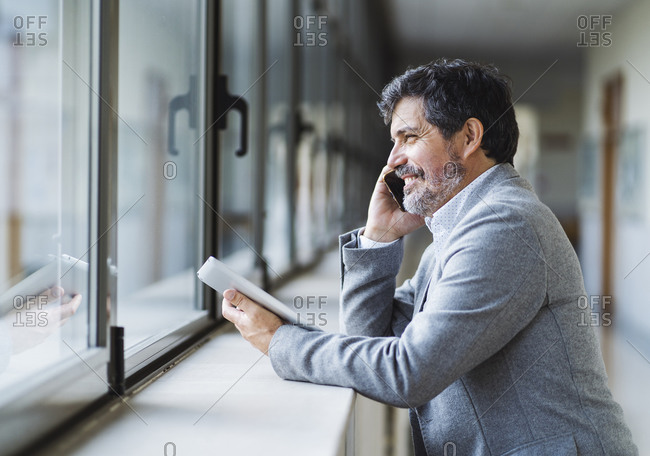 Smiling male professor talking on phone while looking through window in corridor at university