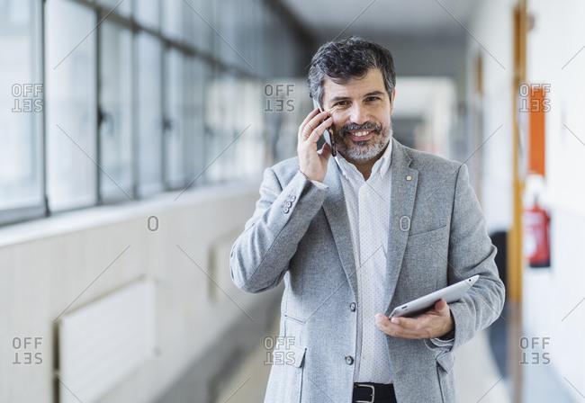 Happy male professor talking on mobile phone holding digital tablet in corridor at university
