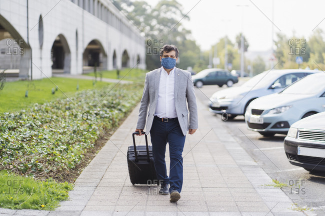 Male professional walking with luggage on sidewalk during COVID-19