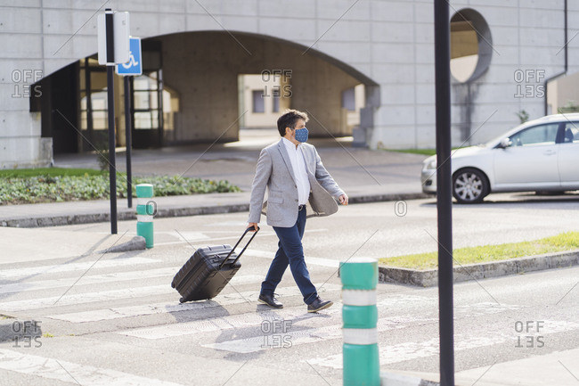 Businessman crossing road with wheeled luggage during COVID-19