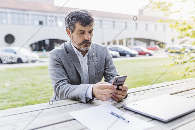 Mature male professional using mobile phone at table against office building
