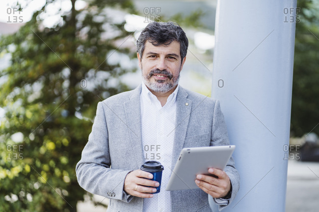 Businessman holding digital tablet and disposable coffee cup by column
