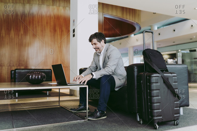 Mature businessman using laptop while sitting in hotel lobby