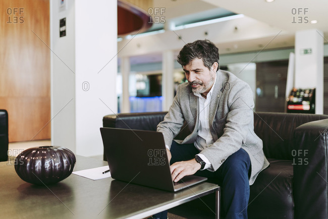 Male entrepreneur using laptop while sitting at lobby in hotel