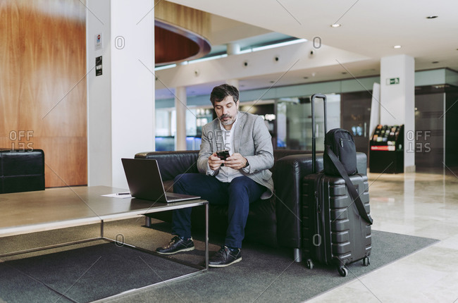 Male professional using mobile phone while sitting in hotel lobby
