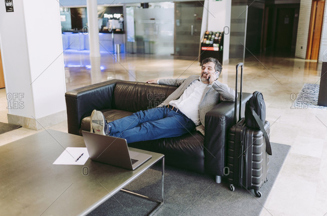 Relaxed businessman sitting in hotel lobby while talking on mobile phone