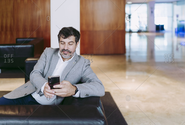 Businessman using mobile phone in hotel lobby