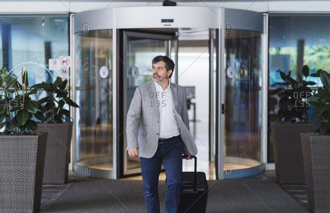 Confident businessman pulling wheeled luggage while entering hotel
