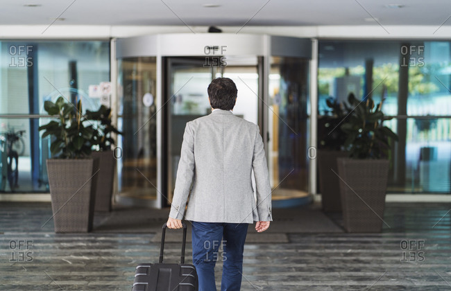 Businessman pulling wheeled luggage while leaving hotel