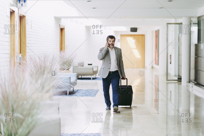 Male entrepreneur on phone pulling wheeled luggage in hotel corridor