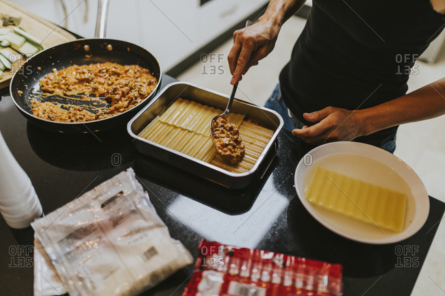 Woman making lasagna while standing in kitchen at home