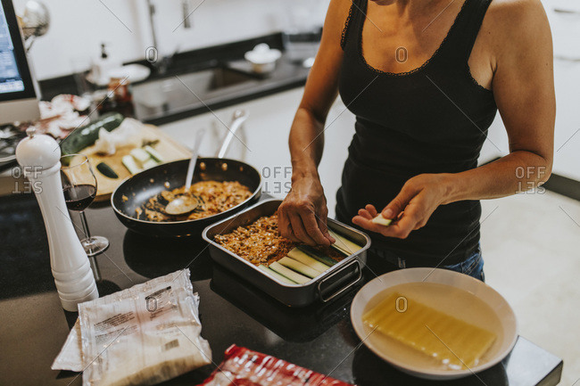 Woman putting chopped zucchini in lasagna cooking tray while standing at kitchen