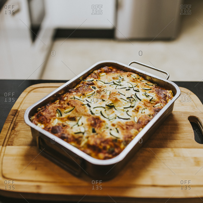 Homemade cooked lasagna with zucchini in tray on cutting board at home