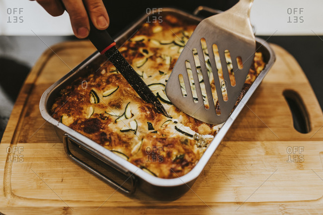 Close-up of woman hand cutting cooked lasagna with zucchini in tray at home