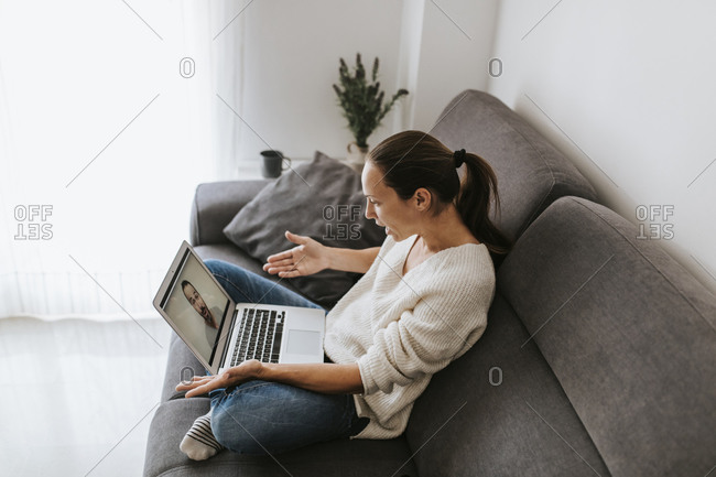 Expressive woman gesturing on video call to friend at home