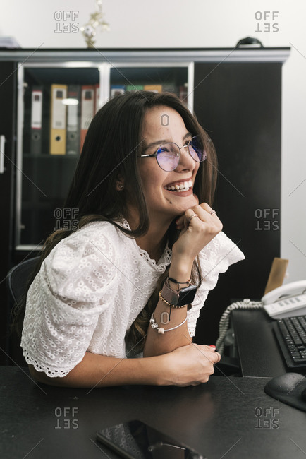 Businesswoman smiling while sitting with hand on chin at office