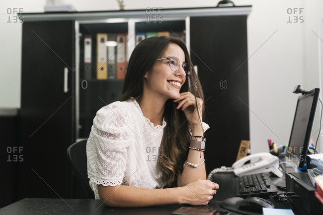 Thoughtful businesswoman smiling while sitting with hand on chin at office
