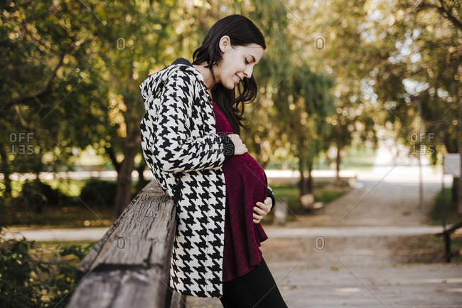 Pregnant woman touching stomach while standing in park