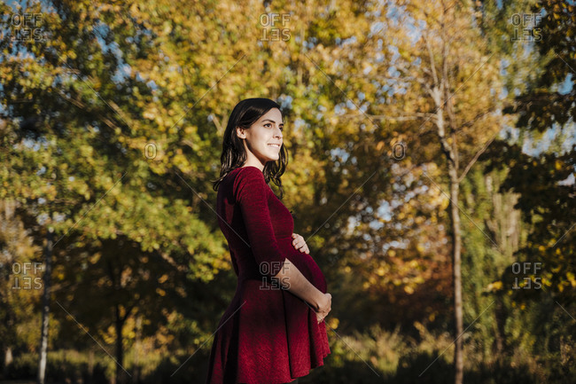 Pregnant woman with hands on stomach standing in park during autumn
