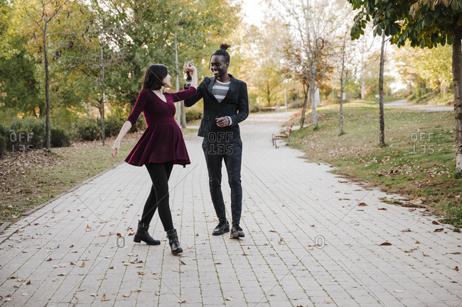 Happy multi ethnic couple dancing in park during autumn