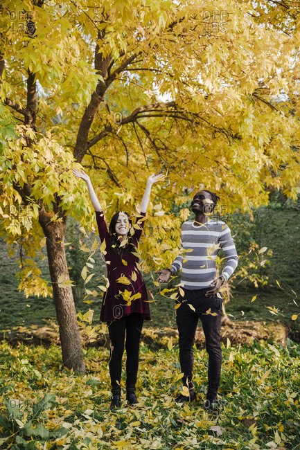 Happy multi ethnic couple playing in park during autumn