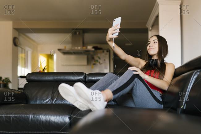 Smiling teenage girl taking selfie through mobile phone while sitting on sofa at home