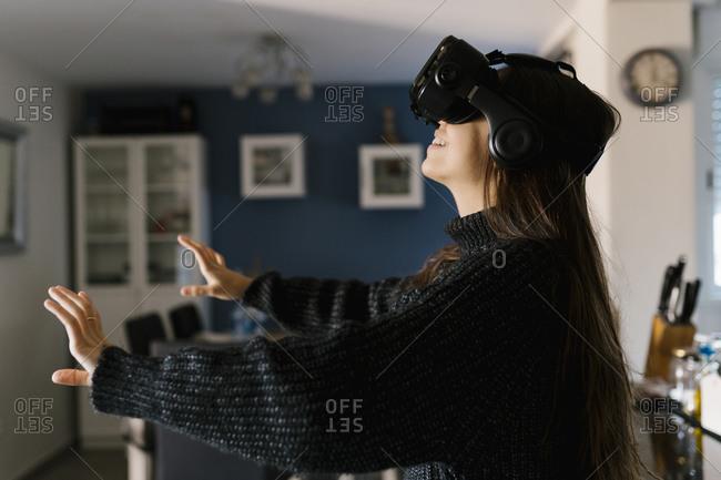 Playful teenage girl wearing virtual reality simulator eyeglasses sitting at home