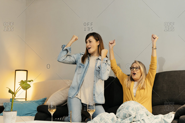 Excited daughter celebrating success with mother while watching TV at home