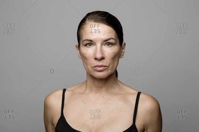 Mature woman with slicked back hair against gray background