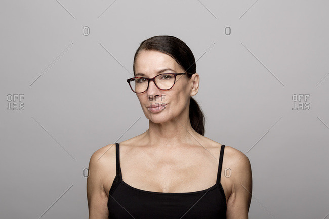Smiling mature woman in black top wearing eyeglasses against gray background