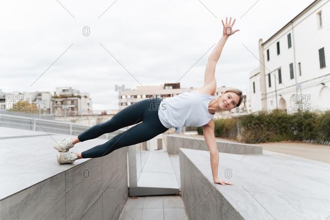 Female athlete doing side plank on retaining wall