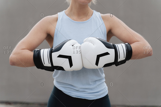 Sportswoman wearing boxing glove standing against wall