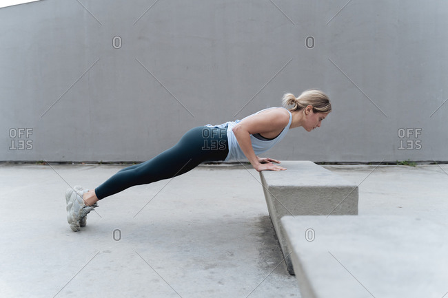 Sportswoman doing push-ups while exercising against wall