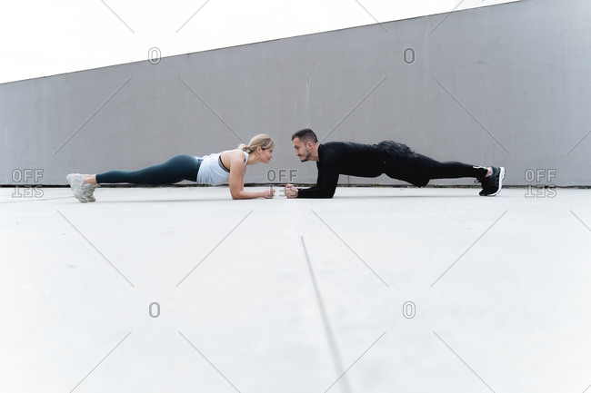 Young couple looking at each other while doing plank against wall