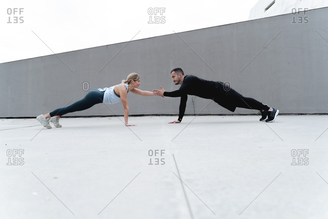 Young couple giving high-five while doing plank against wall